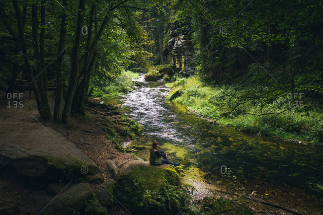 Woman sitting by Hrensko gorge in the Czech Republic
