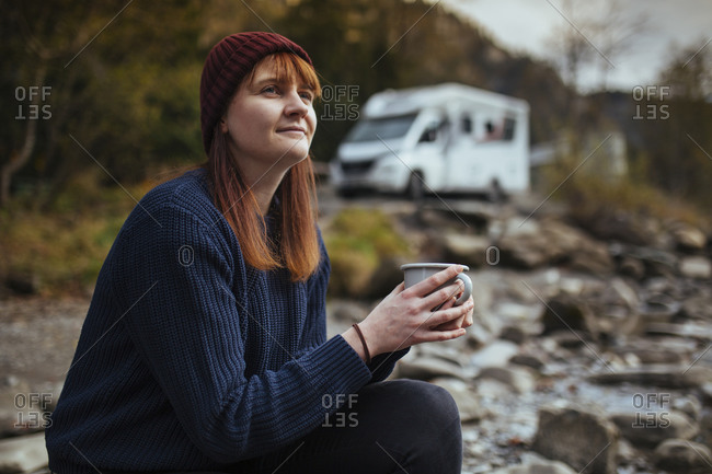 Road trip l woman sits with cup of tea in front of motorhome