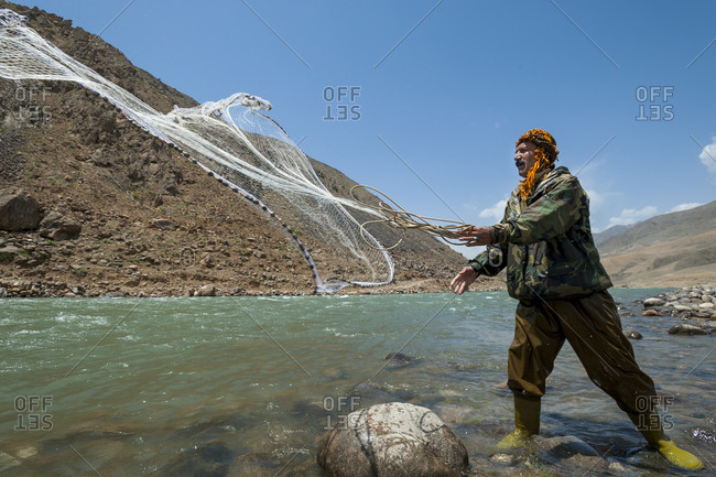 Qalacha, Afghanistan - June 12, 2011: A man from the Panjshir valley in Afghanistan fishes with a throw-net