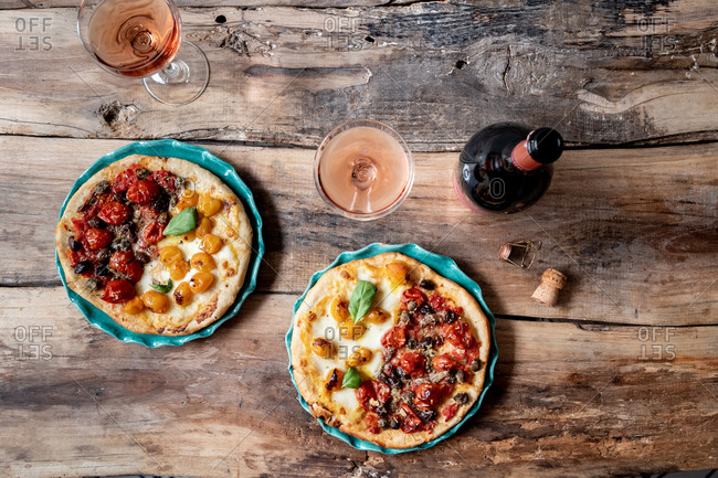 Overhead view of small homemade pizzas served with champagne