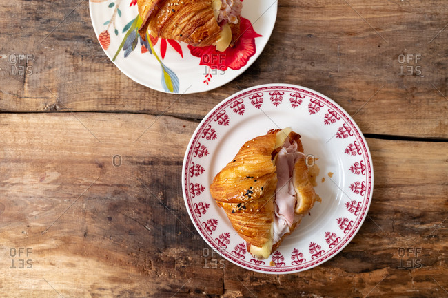 Ham and cheese croissant sandwich on rustic wooden table