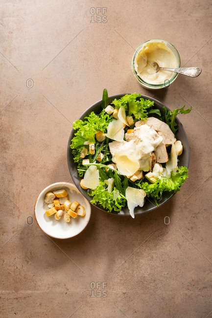 A bowl of lettuce and arugula Caesar salad