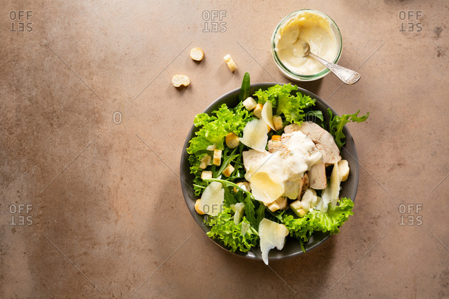 A bowl of lettuce and arugula Caesar salad top view
