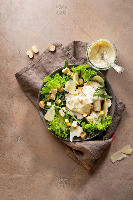 A bowl of lettuce and arugula Caesar salad with napkin
