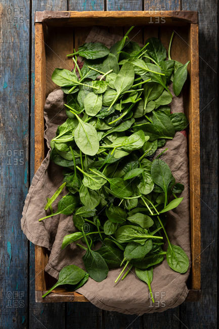 Spinach leaves in a crate on wooden table