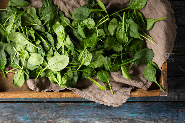 Baby spinach leaves in a crate on wooden table