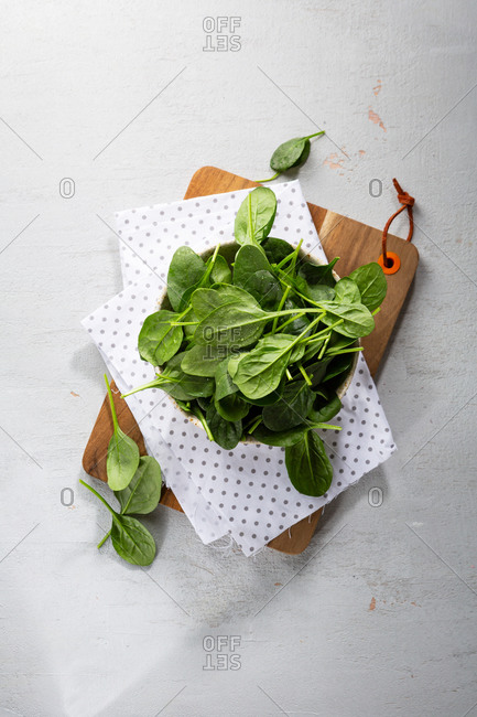 Baby spinach leaves in a bowl on a cutting board