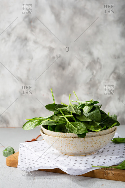 Fresh spinach leaves in bowl on light table