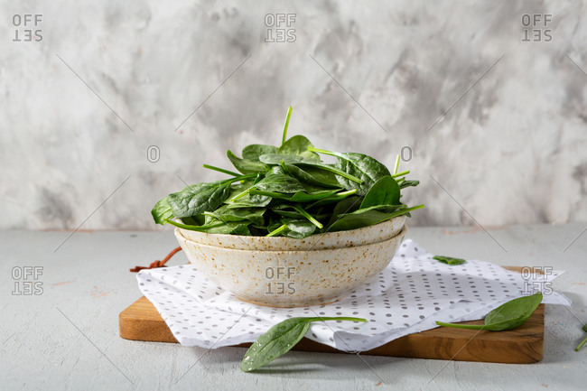 Fresh spinach leaves in bowl on light table side view