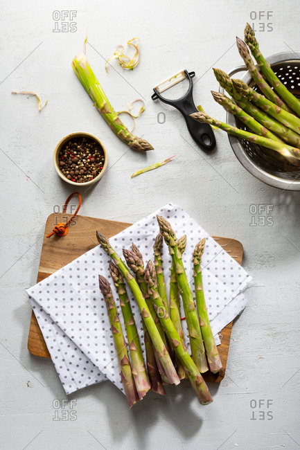 Overhead view of asparagus and colander on light surface while cooking homemade food