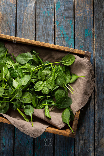 Spinach leaves in a crate on wooden table top view
