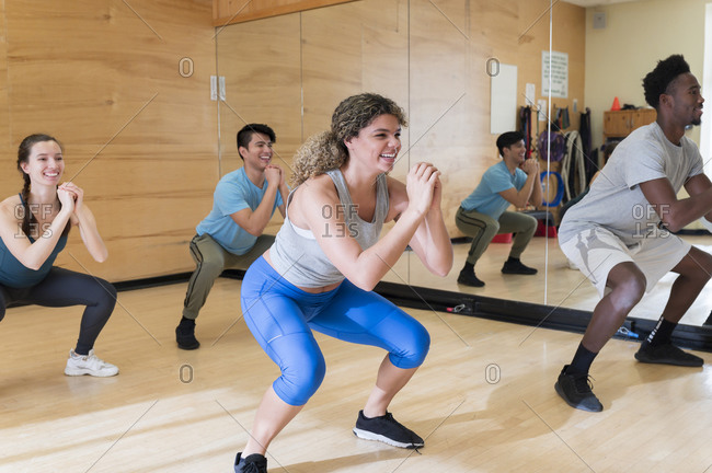 Men and women exercising in workout class