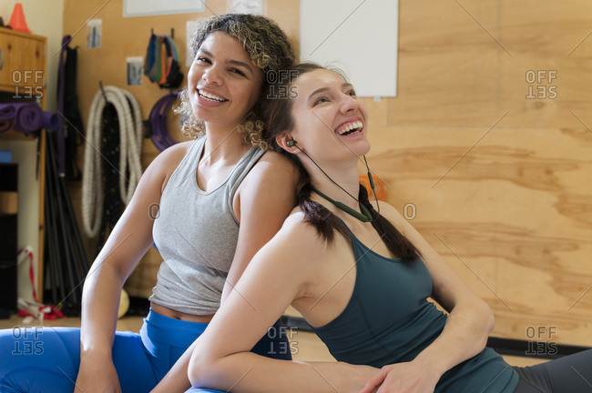 Friends leaning on each other after exercise class�