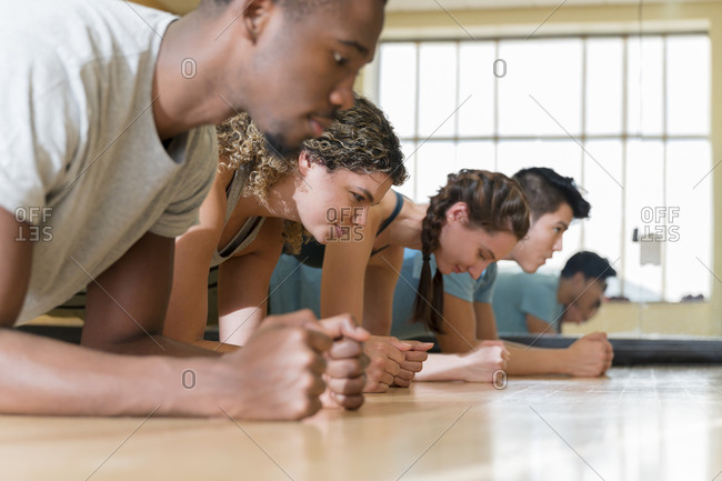 Group of friends doing planks in exercise class�