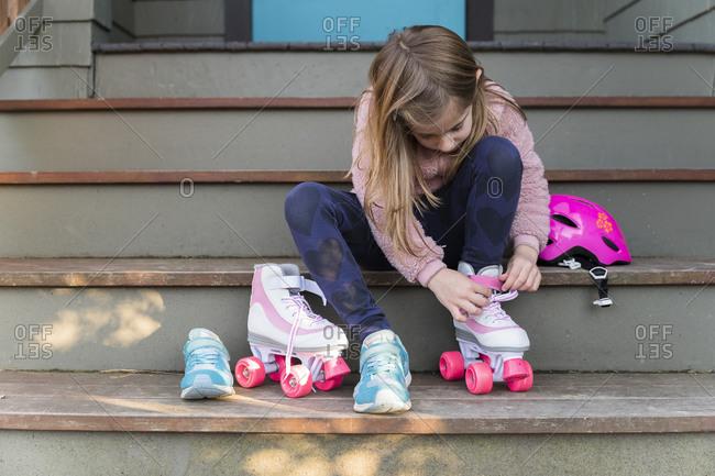 Little girl putting on roller skates