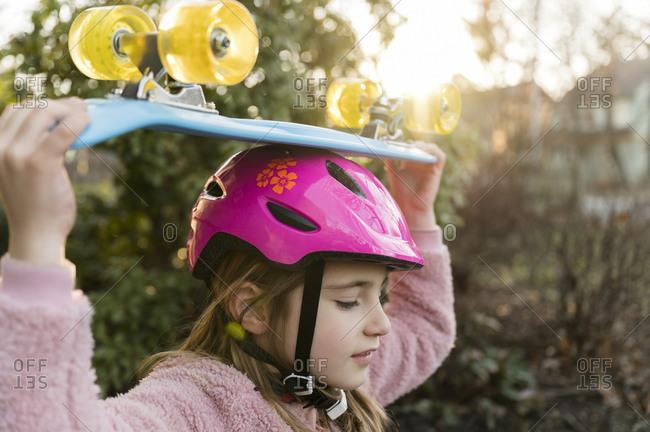 Girl carrying skateboard on head