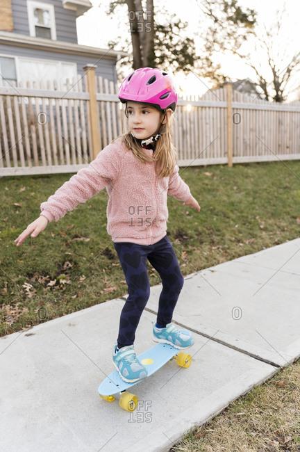 Girl skateboarding down on sidewalk