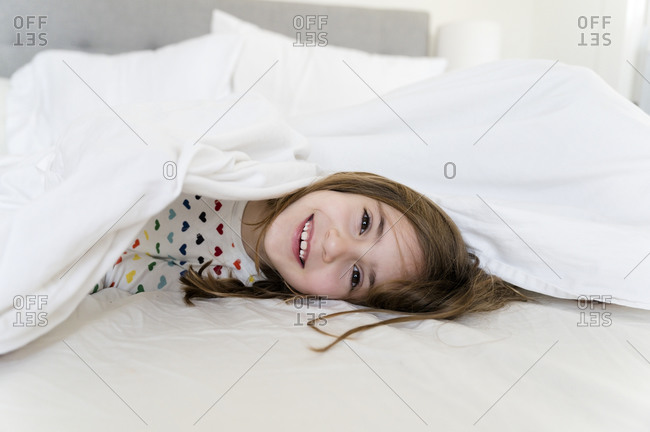 Little girl lying in bed smiling�