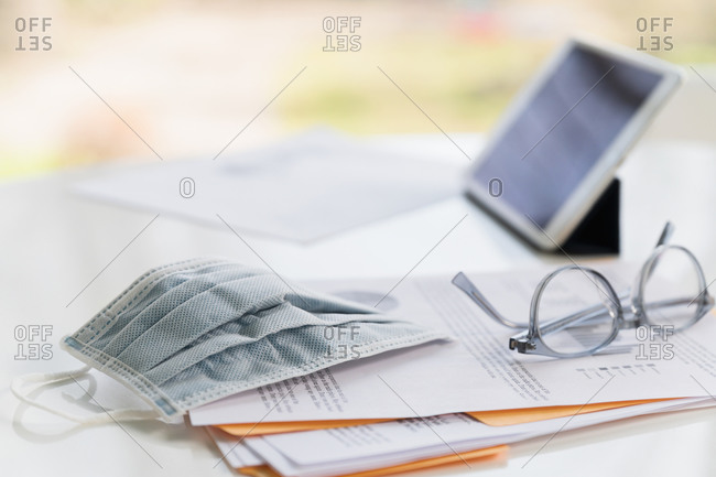 Face mask on business papers and tablet