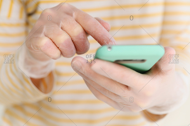 Hands in gloves using smart phone