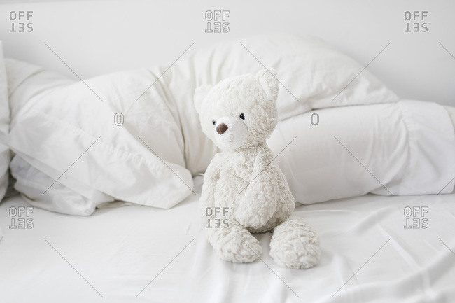 Teddy bear on bed with balnkets