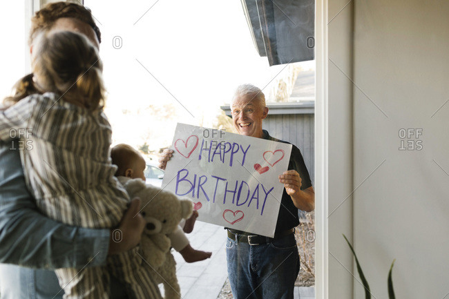 Grandfather showing happy birthday message to family with grandchildren (2-3 months, 2-3) through window