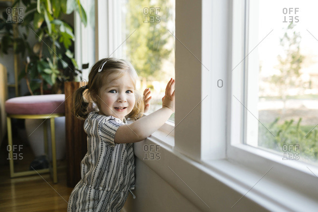Girl (2-3) standing at window