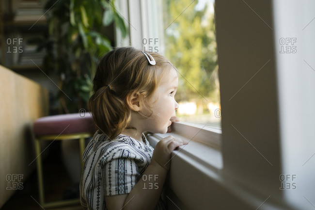 Girl (2-3) looking through window