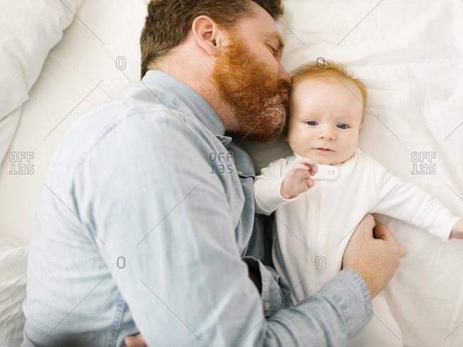 Father kissing baby boy (2-3 months) while lying on bed