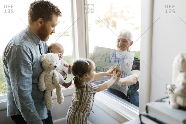 Grandfather visiting family with grandchildren (2-3 months, 2-3) and showing happy birthday sign through window