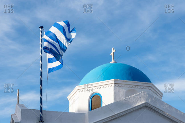 Greek flag and orthodox church in Mykonos, Greece