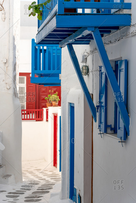 Mykonos island street view with white, blue and red houses in Cyclades, Greece