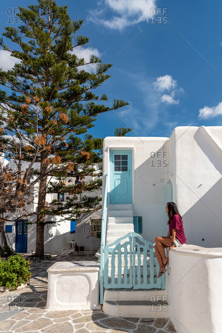 Woman with red t-shirt sitting in front of a blue wooden door in Greece
