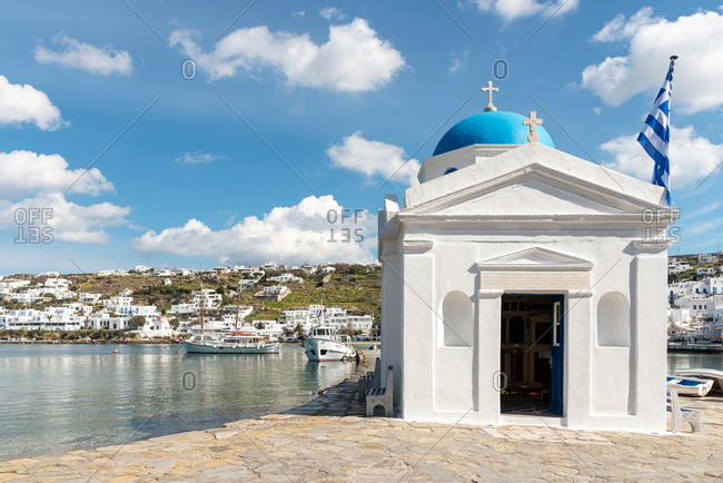 February 13, 2018: Greek church building and Greek flag in Old Port of Mykonos. Mykonos, Greece