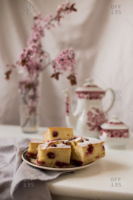 Cherry cake slices on a plate with tea and cherry blossoms