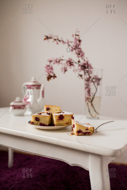 Serving of cherry cake with cherry blossoms and tea