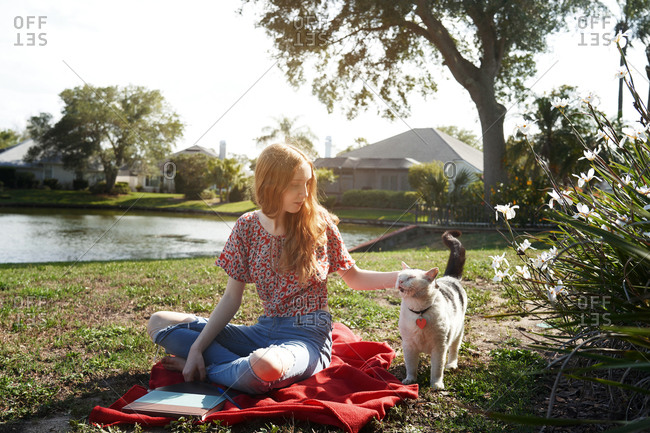 Smiling teenage girl relaxing next to the lake with her pet cat