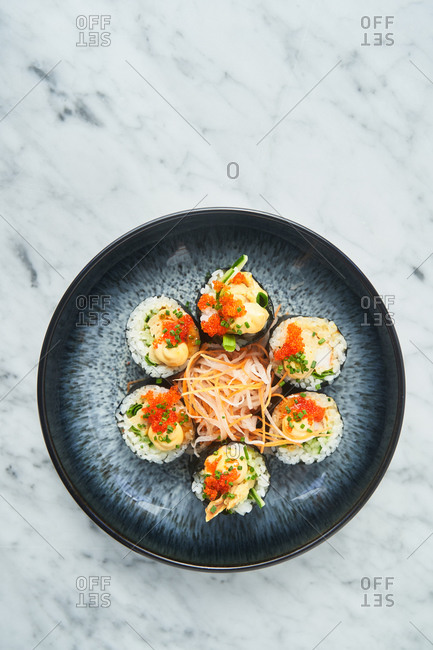 Overhead view of a gimbap dish on white marble surface