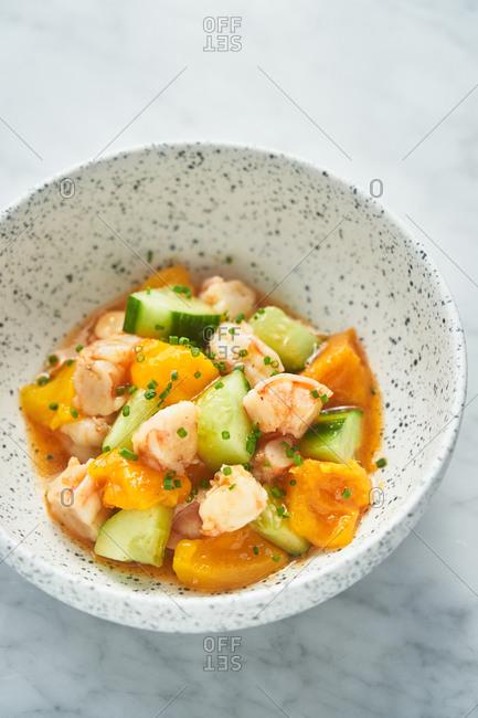 Close up of a mango and cucumber salad with shrimp