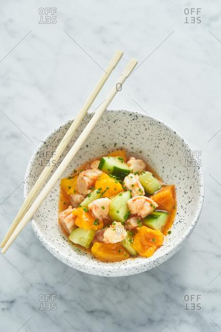 Asian mango and cucumber salad with shrimp and chopsticks