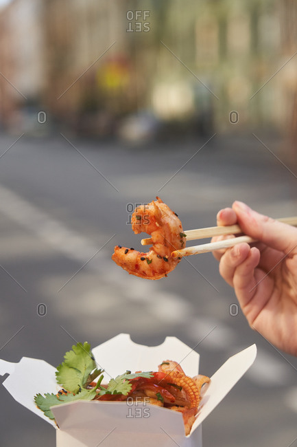 Person holding shrimp above takeout box with chopsticks