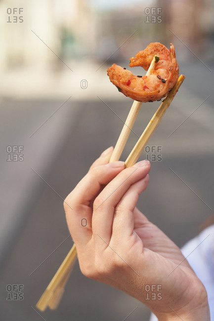 Person holding a large shrimp with chopsticks