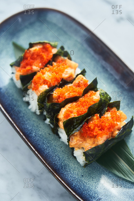 Close up of a sushi appetizer with rice, fish and spicy mayo