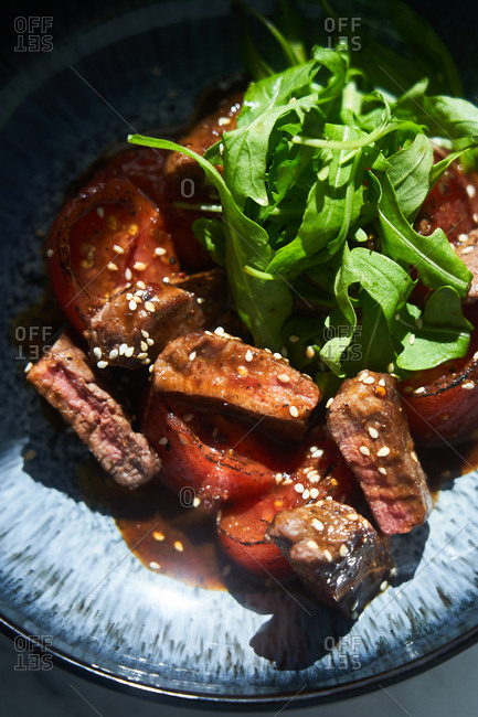 Asian sesame beef dish with arugula salad