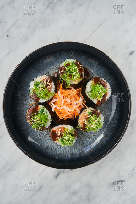 Overhead view of a gimbap dish on a black plate on white marble surface
