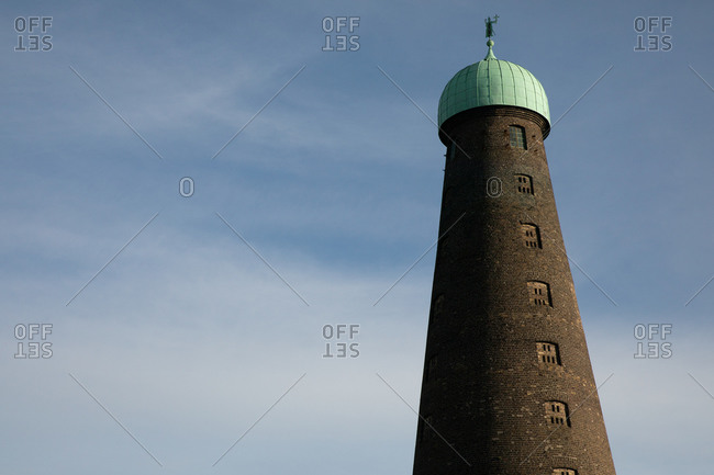 Brick conical tower against blue cloudy sky