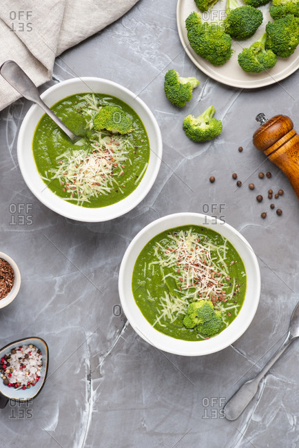 Overhead view of two bowls with green broccoli cream soup served with ground cheese parmesan and linen seeds