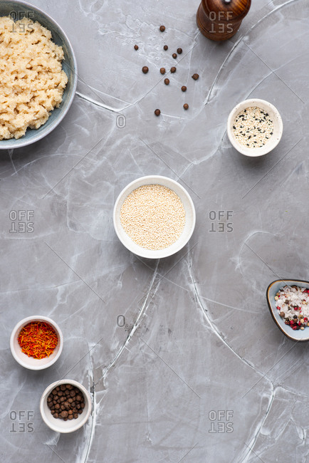 Overhead view of two ceramic bowls with quinoa and spices over gray background
