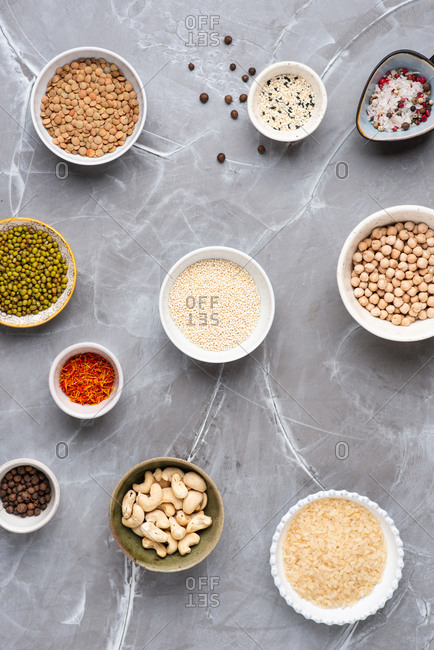 A collection of seeds and grains on grey background in ceramic bowls, quinoa, lentils, cashew nuts, rice, chickpeas, mung beans, saffron, sesame seeds
