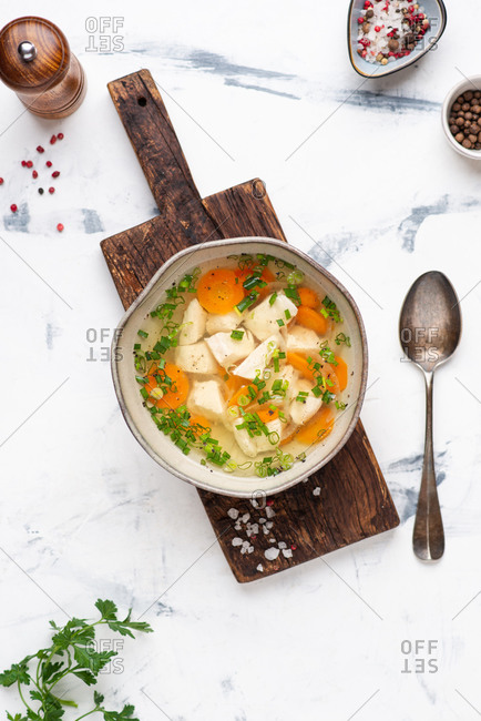 Served bowl of chicken soup from above. Broth with chicken, vegetables and greens